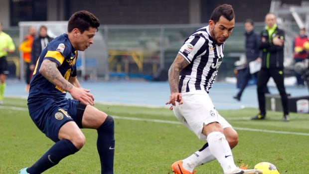 Juventus' Carlos Tevez, right, is chased by Verona's Juan Manuel Iturbe at Bentegodi stadium in Verona, Italy, Sunday, Feb. 9, 2014.