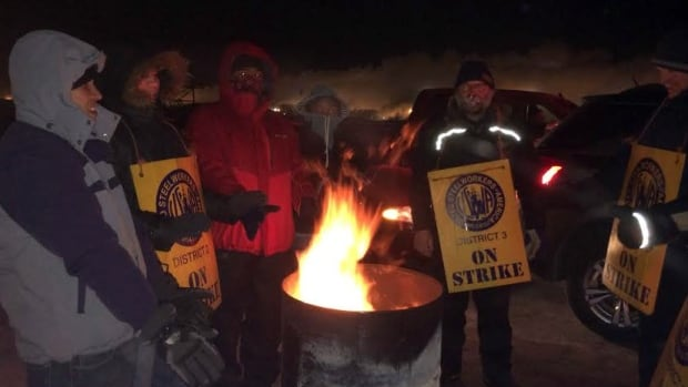 Striking Degelman workers huddled for warmth amid temperatures that dipped below -30 C on Monday.