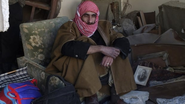 A man sits near his belongings inside a damaged room as he waits to be evacuated from a besieged area of Homs on Tuesday.
