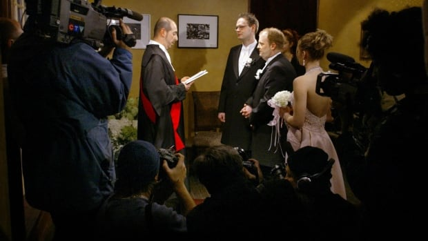 Members of the media look on as Justice Harvey Brownstone marries Scott Gould and Paul Langsholt (right) from Rockford, Ill during a same-sex marriage in Toronto, Saturday February 14, 2004. Gould and Langsholt were one of seven same-sex couples who made the trip to Canada to be married.