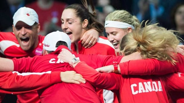 Canada's Eugenie Bouchard, second right, celebrates with teammates after defeating Vesna Dolonc from Serbia during a Federation Cup tennis match in Montreal on Sunday.