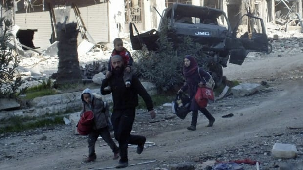 Civilians run towards a meeting point to be evacuated from a besieged area of Homs on Sunday. Over 1,000 civilians have already fled the area, which has been under siege for 20 months.