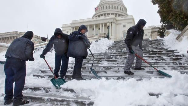 Workmen clear snow from the steps on Capitol Hill in Washington.  The winter weather has turned D.C. into a ghost town.  Businesses are closed, schools are shut and the streets are empty.