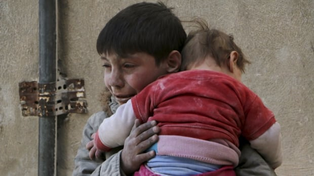 A boy holds his baby sister saved from under rubble after what activists say was an airstrike by forces loyal to Syrian President Bashar al-Assad in Aleppo. More than 130,000 people have died in the conflict since it began three years ago.