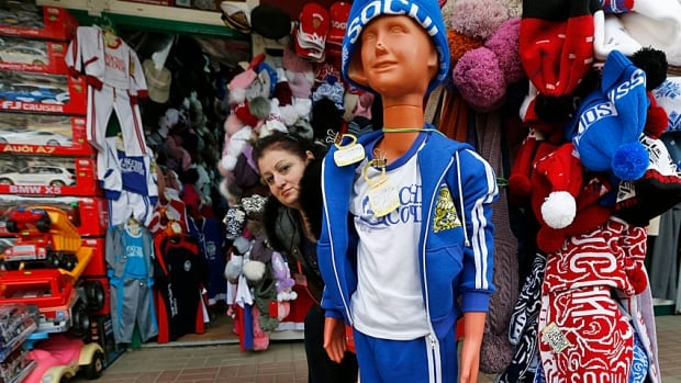 A woman looks out from behind Olympic-themed souvenirs on display at the central market in Adler, near Sochi. Some of them may even be official.