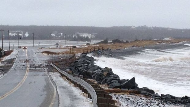 Pounding waves push rocks onto the road at Lawrencetown beach.