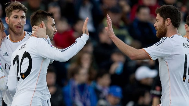 Sergio Ramos, left, of Real Madrid CF celebrates scoring their third goal with teammates Jese Rodriguez, second from left, and Xabi Alonso, right, during a La Liga match in Getafe, Spain.