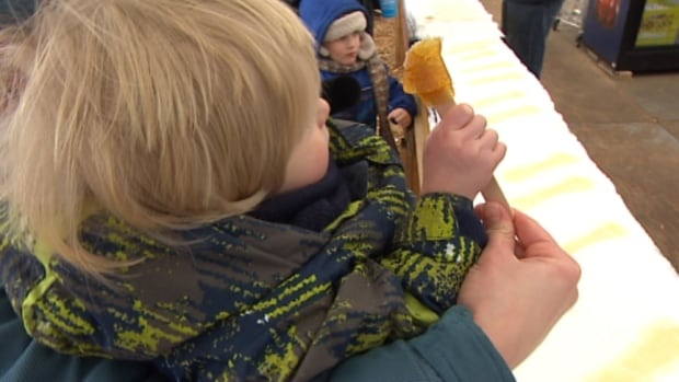 A child enjoys maple taffy on Sunday from the Sugar Shack at Festival du Voyageur, one of numerous Winnipeg attractions open on Louis Riel Day.