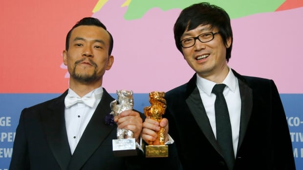 Diao Yinan, right, director of Bai Ri Yan Huo (Black Coal, Thin Ice) poses with his Golden Bear for Best Film next to actor Liao Fan, who poses with his Silver Bear for Best Actor during a news conference after the awards ceremony of the 64th Berlinale International Film Festival in Berlin February 15, 2014.