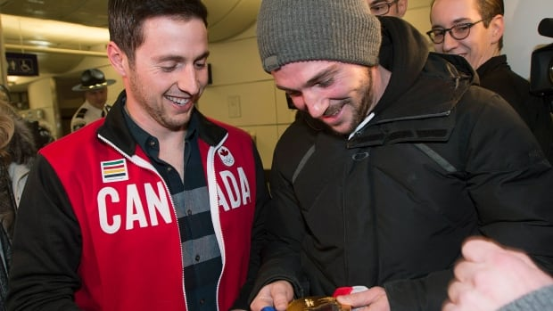Canadian freestyle moguls skier Alexandre Bilodeau, left, shows one of his friends holding his 2014 Sochi Winter Olympic gold medal on his arrival back from the Olympic games at Trudeau Airport in Montreal, Sunday, February 16, 2014.