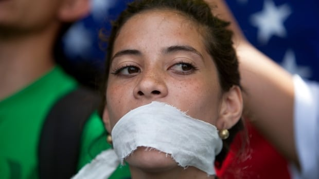 A demonstrator covers her mouth with a rag to protest government censorship, during a march to Venezuelan Telecommunications Regulator Office on Feb. 17.
