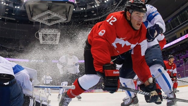 Canada forward Patrick Marleau hits the ice against Finland defenseman Juuso Hietanen in the first period of a men's ice hockey game at the 2014 Winter Olympics, Sunday, Feb. 16, 2014, in Sochi, Russia. (AP Photo/Mark Blinch, Pool)