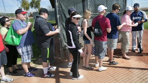 Fans line up for an autograph from Seattle Mariners second baseman Robinson Cano, far right, in Peoria, Ariz., on Tuesday.