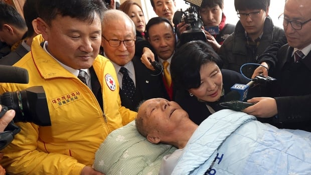 Kim Sun-kyum, 91, is helped by a Red Cross official as he arrives to take part in family reunions with his North Korean family members at a hotel in Sokcho, South Korea, Wednesday. About 500 South Koreans will be reunited with their North Korean relatives at the Diamond Mountain in North Korea from Feb. 20 to 25.
