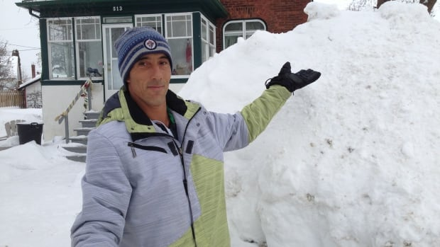 """Derek Bousquet stands in front of a snowbank near his home on Luci Court on Thunder Bay's south side. Bousquet says he's seen worse winters growing up in Winnipeg, but """"we have enough snow"""" for this year in Thunder Bay."""