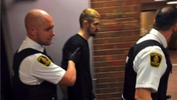 Justin Michael Chipman, 26, is led into provincial court in St. John's Wednesday afternoon.