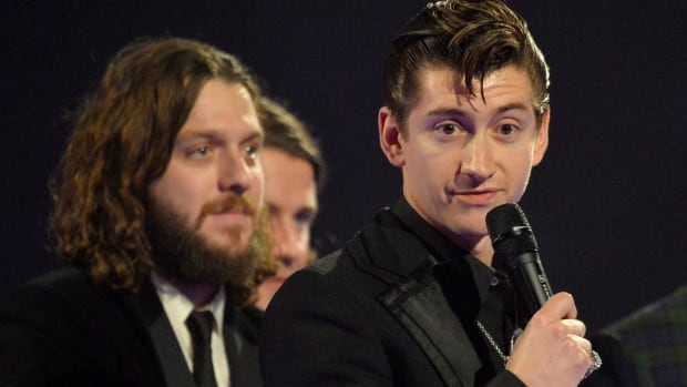 Alex Turner, right, of the Arctic Monkeys talks after the band was presented with the British Album award at the BRIT Awards, celebrating British pop music, at the O2 Arena in London, England on Wednesday.