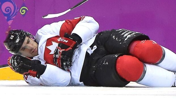 Canada's John Tavares lies in pain on the ice at the Bolshoy Ice Dome in Sochi, Russia, on Wednesday after suffering a left knee injury during the second period of his team's 2-1quarter-final win over Latvia. Tavares will sit out the balance of the NHL regular season.
