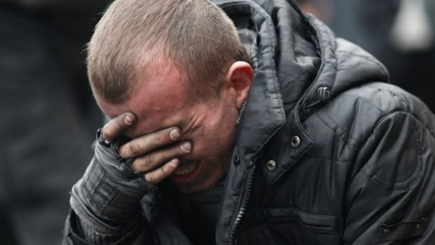 An anti-government protester breaks down following clashes with riot police in Independence Square in Kyiv Thursday. Many civilians were killed in fresh fighting, which shattered an overnight truce declared by Ukrainian President Viktor Yanukovich. A presidential statement said dozens of police are also dead or wounded.