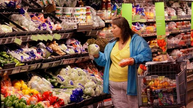 A shopper picks out groceries while at the Wal-Mart Super Center in Springfield, Ill. The retailer saw a decline in same-store sales of groceries after food stamp programs were cut.