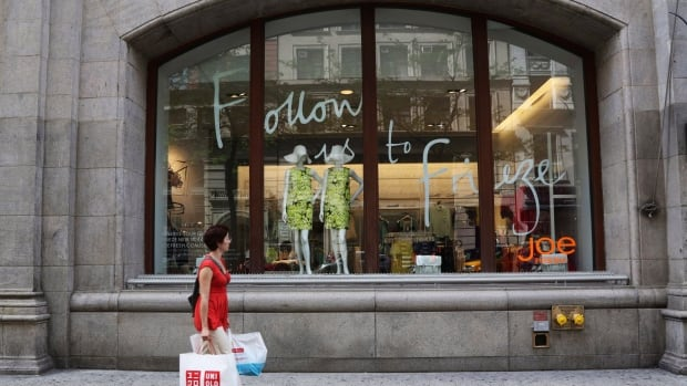 This photo from May 2013 shows a shopper walking past the Joe Fresh store on Fifth Avenue in New York.  Joe Fresh plans a major international expansion, says parent company Loblaw.