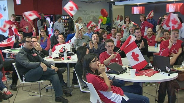 Canadian Tire employees show their support for the men's hockey team while they watch its quarter-final game against Latvia.