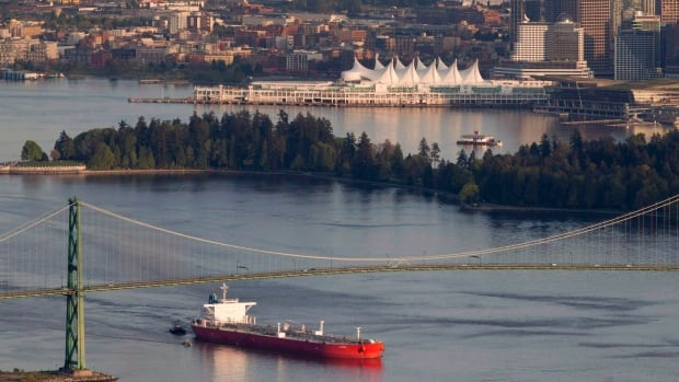 "A oil tanker is guided by tugboats as it goes under the Lions Gate Bridge at the mouth of Vancouver Harbour. The resource sector is ""resilient"" and exports are set to grow in 2014, says the Conference Board of Canada"