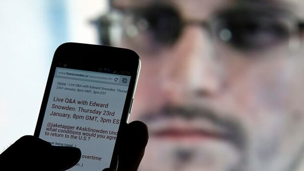 A man uses his cellphone Edward Snowden answers questions on Twitter in January 2014.