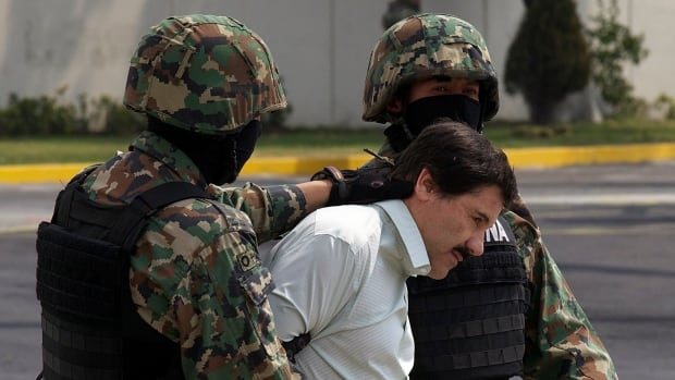 "Joaquin ""El Chapo"" Guzman is escorted to a helicopter in handcuffs by Mexican navy marines at a navy hangar in Mexico City, Mexico, on Saturday. A senior U.S. law enforcement official said that Guzman, the head of Mexico's Sinaloa Cartel, was captured alive overnight in the beach resort town of Mazatlan. (Dario Lopez-Mills/Associated Press)"