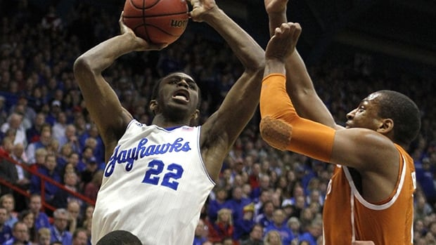 Andrew Wiggins of the Kansas Jayhawks, left, takes a shot against the Texas Longhorns in the first half on February 22, 2014 in Lawrence, Kansas.