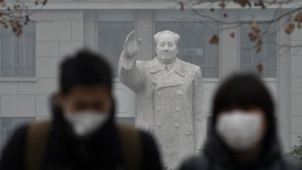 People walk in front of the statue of late Chinese leader Mao Zedong during a hazy day in Shanghai Dec. 26, 2013.