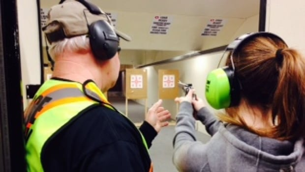 Don Goodine teaches 20-year-old UNB student how to shoot.