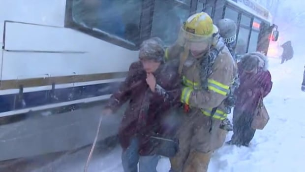 A firefighter helps an elderly woman after a fire broke out at a seniors apartment complex.