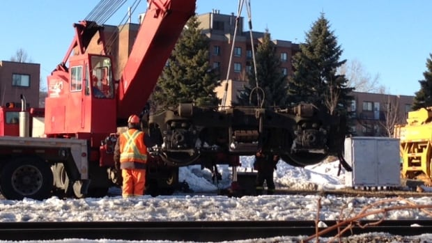 Work crews lift the disassembled wheels from the car of a CN freight train that derailed in St-Henri early Sunday morning.