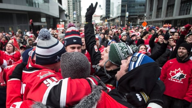 Fans are seen celebrating in Toronto's Maple Leaf Square on Sunday after Team Canada scored its third goal against Sweden in the gold-medal final in Sochi.