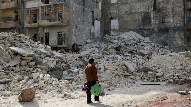 A man walks past damage after what activists said was an air strike by forces loyal to Syria's President Bashar al-Assad in the Al-Maysar neighbourhood of Aleppo on February 23, 2014.