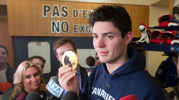 Montreal Canadiens and Team Canada goaltender Carey Price shows his gold medal to the media at the team's practice facility in Brossard, Que.