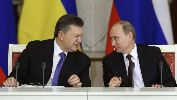 Ukrainian President Viktor Yanukovych, left, winks in a 2013 photo to his Russian counterpart Vladimir Putin. Yanukovych is now in hiding following his ouster and allegations of mass murder. Analysts say Russia is not likely to seek his prosecution, though it is not likely to support him either.