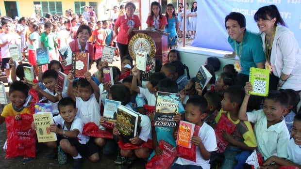 Author Mitch Albom, seen in the top corner second from right, poses with Filipino teachers and school children on Monday, during a visit to typhoon-ravaged Tacloban in central Philippines.