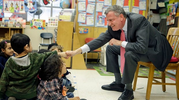 New York City Mayor Bill de Blasio shakes hands with a future voter after setting out his plans for universal pre-kindergarten in New York City. A tax on wealthy New Yorkers will pay for it.