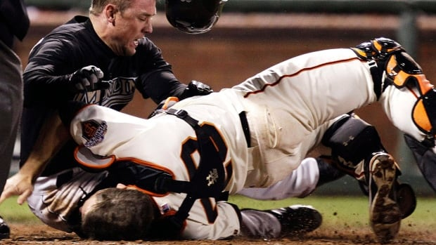 """Giants catcher Buster Posey, bottom, broke a bone in his lower left leg and tore three ligaments in his ankle in this collision with Scott Cousins of the Florida Marlins in a May 25, 2011 game. He says baseball's new rule does a good thing by eliminating """"malicious collisions."""