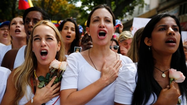 Female opposition supporters in white clothes marched from a western Caracas neighbourhood to a nearby National Guard base, carrying photographs of victims of alleged brutality by the security forces.