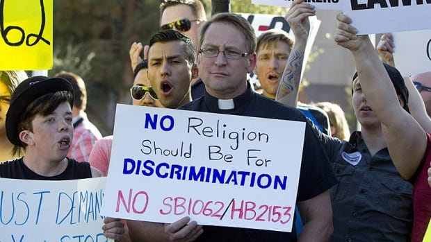Opponents of Arizona's religious freedom bill, which would have allowed for discrimination against gays, rally at the state legislature on Friday. The bill passed but was rejected by Governor Jan Brewer on Wednesday.
