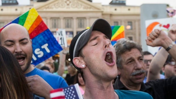 Demonstrators celebrate after hearing that Arizona Gov. Jan Brewer was going to veto the controversial anti-gay bill. The bill was designed to give added protection from lawsuits to people who assert their religious beliefs in refusing service to gays.