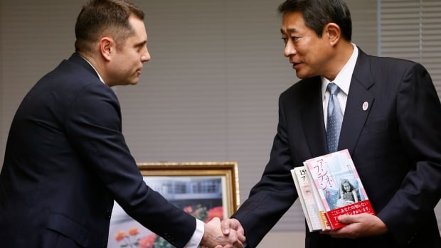 Israeli Embassy to Japan representative Peleg Lewi, left, shakes hands with Suginami Ward Mayor Ryo Tanaka as he hands over Anne Frank-related books to public libraries at the Suginami Ward Office in Tokyo on Thursday.