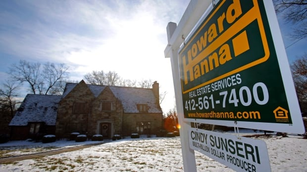 A a for sale sign hangs in front of a house in Mount Lebanon, Penn., on Jan. 9. Home prices fell in January for the third-straight month as cold weather continued to deter buyers.