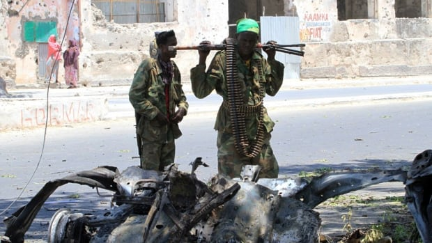 Somali government soldiers look at the wreckage of a mangled car used by a suicide bomber at the scene of Thursday's bomb attack next to a tea shop in the suburbs of capital Mogadishu.