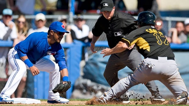 The Pirates' Gaby Sanchez, right, stops before getting tagged out by Blue Jays third baseman Maicer Izturis during the fourth inning. Colby Rasmus drove in two runs to lead Toronto a 4-2 pre-season win over Pittsburgh on Friday in Dunedin, Fla.
