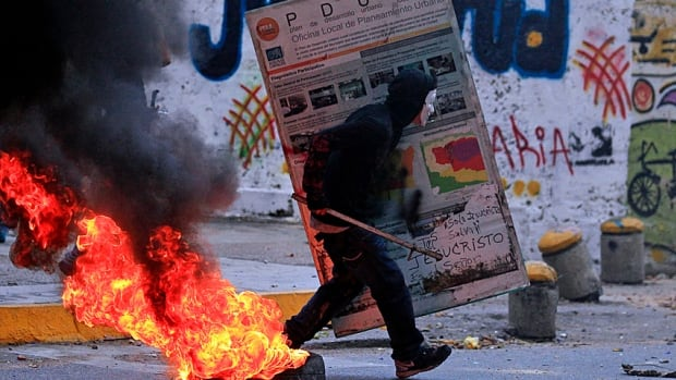 An opposition demonstrator runs with a makeshift shield during clashes with police at Altamira Square, across the street from the Canadian Embassy, in Caracas on Thursday.