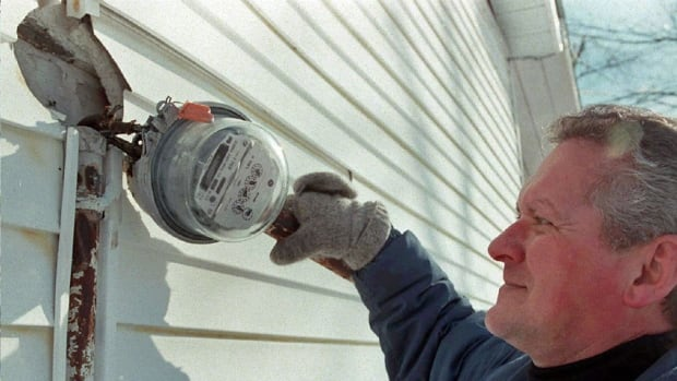 An Ontario resident examines an electricity meter. An unusually cold winter in Canada has caused utility bills to soar amid high energy demands for home heating.